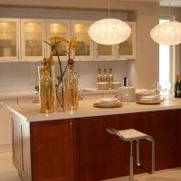 белая прямая кухня с большим островом в качестве обеденной зоны
