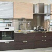 кухня с фасадами из ЛДСП и маленьким встроенным холодильником