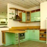 угловая зеленая кухня с глянцевыми фасадами и барной стойкой